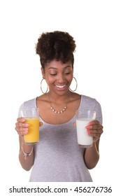 Portrait of a woman choosing between orange juice and milk. Woman appears to be choosing the milk.