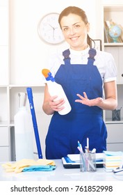 Portrait of woman cleaning the office with cleaners, gloves and mop