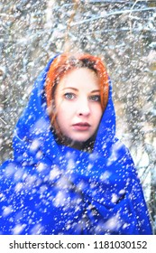 Portrait of a woman in a cold winter. Portrait of woman in winter clothing looking at camera in snowy park.