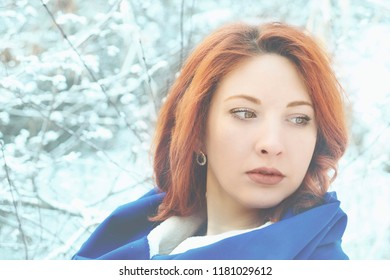 Portrait of a woman in a cold winter. Winter woman in snow looking outside on snowing cold winter day.