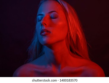 Portrait of a woman with colored light and dark background.
