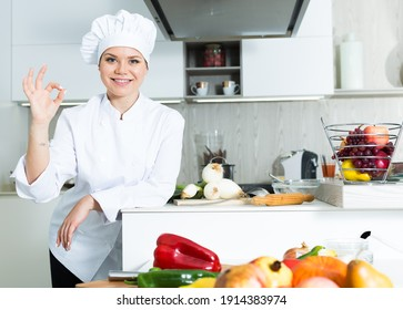 Portrait of woman cook who is standing on her work place in the kitchen at the cafe.