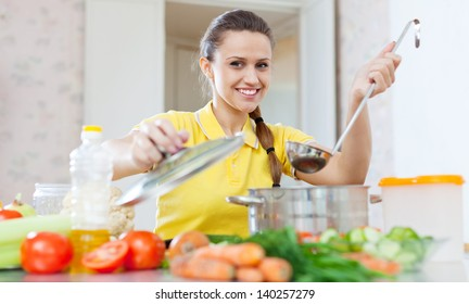 Portrait of  woman cooking  vegetarian food in saucepan at home kitchen
