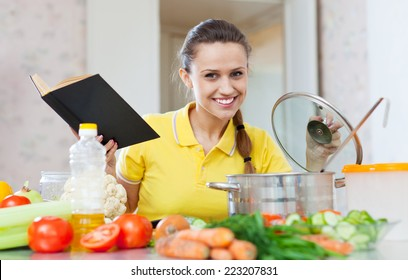 Portrait of  woman cooking  vegetarian food with cookbook