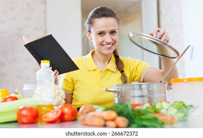 Portrait of  woman cooking  vegetarian food with cookbook at home kitchen