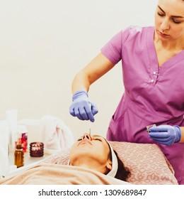 Portrait of woman cosmetologist applying peeling gel of clients face
