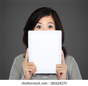 portrait of woman covering her face with tablet computer. isolated over white background