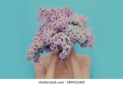 Portrait of woman covering her head with a bouquet of lilac flowers on blue background