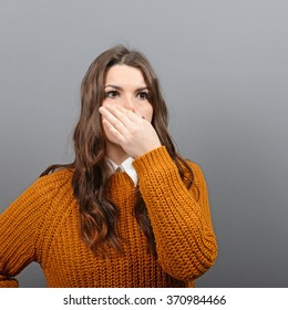 Portrait of woman covering nose with hand showing that something stinks against gray background