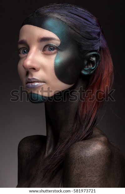 Portrait of a woman with creative make-up on a gray background. With bright colors on her hair and face. Art beauty.
