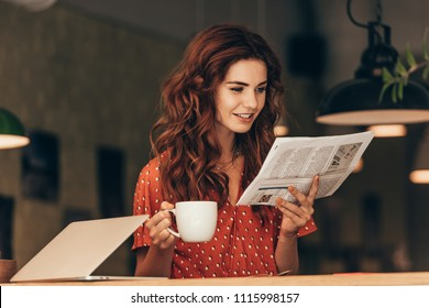 portrait of woman with cup of coffee reading newspaper at table with laptop in cafe