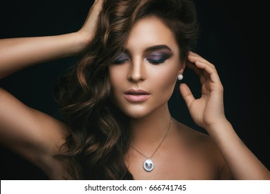 Portrait of woman with curly hair, beautiful make-up and expensive pendant with a diamond on her neck