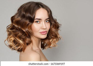 Portrait of a woman with curly hair. Haircut. Shine and hair care