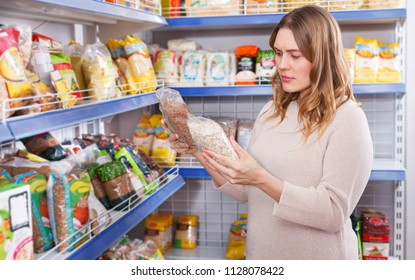 Portrait of woman customer choosing a groats in the grocery food shop