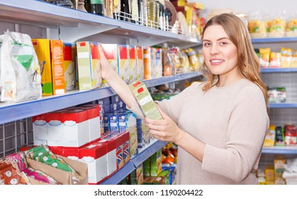 Portrait of woman customer choosing groats in the grocery food shop