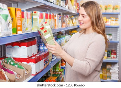 Portrait of woman customer choosing groats in grocery food shop