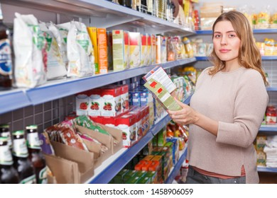 Portrait of woman customer choosing groats at a grocery food shop
