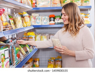 Portrait of woman customer choosing a groats in grocery food shop