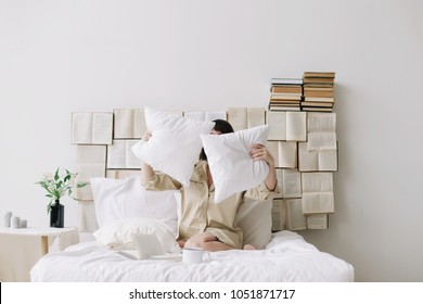 Portrait of a woman with dark hair throwing up pillows in bed in the morning at home. Beautiful young brunette with pillows and a cup of coffee in the bedroom. Good morning. Lifestyle.