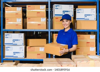 Portrait of woman delivery staff in blue uniform holding parcel box in warehouse