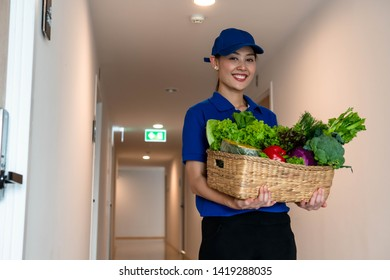 Portrait of woman delivery staff holding basket of vegetables delivering to customer in apartment