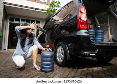 portrait of woman desperately try to carry a heavy gallon of water and put in the car trunk