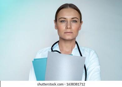 Portrait of a woman doctor holding medical records, isolated on blue background, Dr. at work, intern in the hospital, healthcare industry