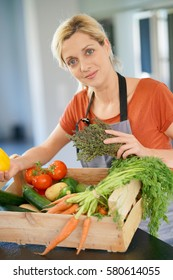 Portrait of woman in domestic kitchen holding basket of fresh vegetables