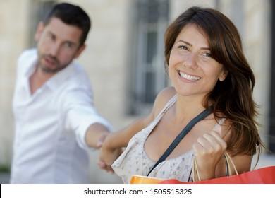 portrait of a woman dragging husband shopping