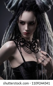 Portrait of woman with dreads and festive black gothic dress posing on dark background