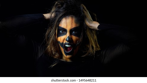 portrait of a woman dressed as halloween pumpkin. Woman with a challenging look.Woman With hands on head screaming in fear. black background.