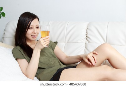Portrait of a woman drinking beer in a room