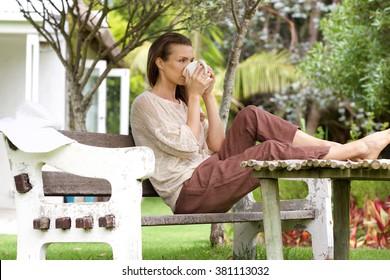 Portrait of a woman drinking tea outside in backyard