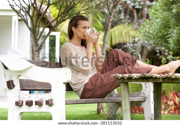 Porträt einer Frau, die im Garten im Freien Tee trinkt