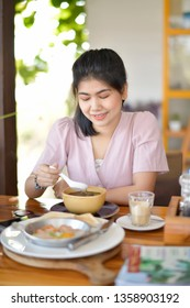 Portrait of woman eating breakfast.