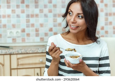 Portrait of woman eating cereals at home.