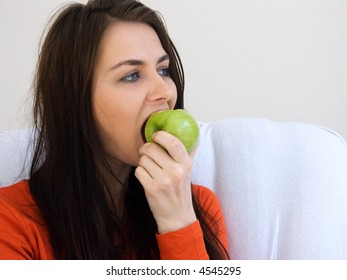 A portrait of a woman eating a green apple.