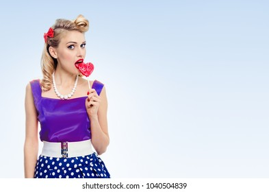 Portrait of woman eating heart shape lollipop dressed in pinup style dress in polka dot, with copyspace area for slogan or advertising text message, on blue background. Caucasian blond model.