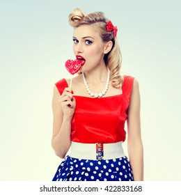 Portrait of woman eating heart shape lollipop dressed in pinup style dress in polka dot. Caucasian blond model posing in retro fashion and vintage concept studio shoot.
