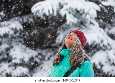 A portrait of a woman enjoying snowflakes falling down on her face on a cold snowy day in the forest