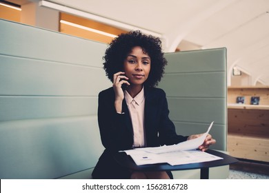 Portrait of woman entrepreneur in trendy wear doing business checking information from papers, proud young female owner looking at camera holding blanks and making mobile conversation with partner