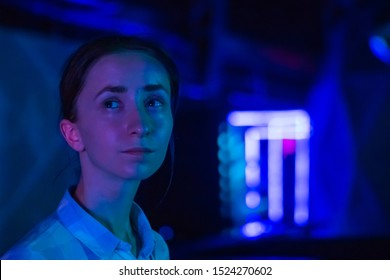 Portrait of woman face looking around at modern immersive exhibition with low light illumination. Blurry bokeh background. Education, digital art and entertainment concept
