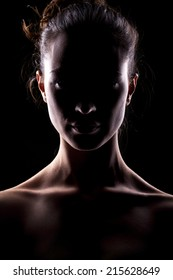 portrait of a woman with the face in shadow on a dark background