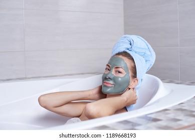 Portrait of a woman in facial alginate mask lying in the retro bath in the bathroom.
