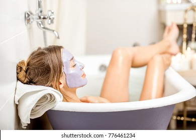 Portrait of a woman in facial alginate mask lying in the retro bath in the bathroom
