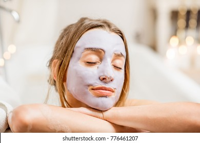 Portrait of a woman in facial mask lying in the retro bath in the bathroom