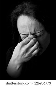 portrait of a woman feeling pain, frowning with hand on head with black background