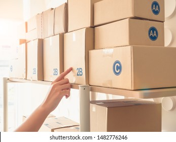 Portrait of woman finger pointing on the box that show to selecting or counting goods on the shelf in stockhouse