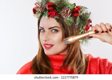 Portrait of a woman with a fir wreath with cones on her head, holds in her hand a nozzle for a cosmetic procedure.Rf lifting procedure in a beauty parlour.