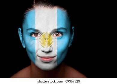 Portrait of a woman with the flag of the Argentine painted on her face.
